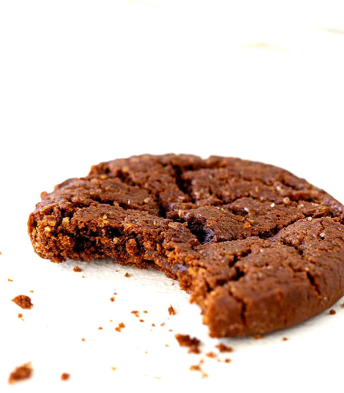 Bitten ginger molasses cookies on white surface