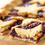 Squares of raspberry linzer torte on light colored wooden board