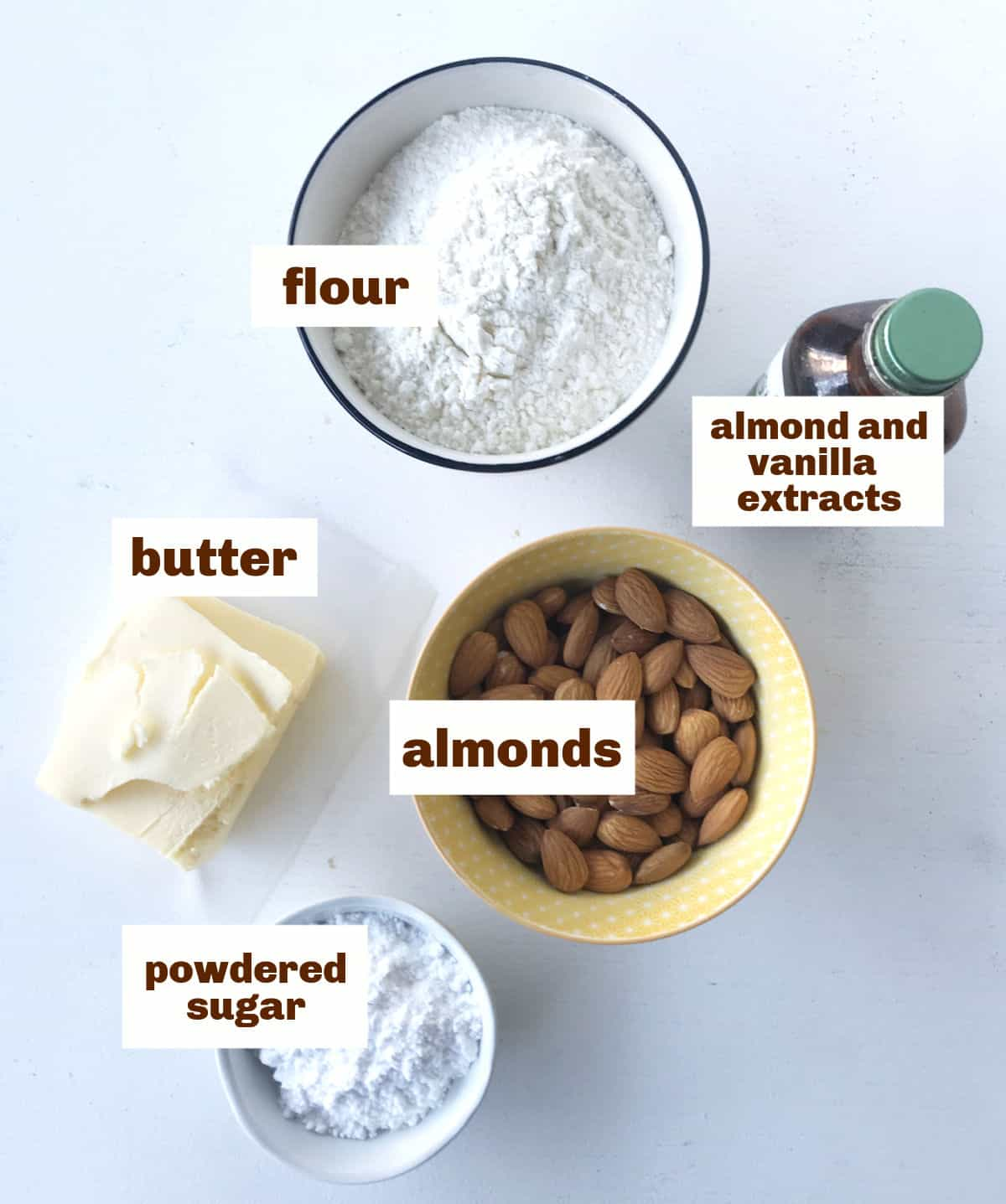 Bowls with almonds, flour and sugar, chunk of butter and a small bottle on a whitish surface