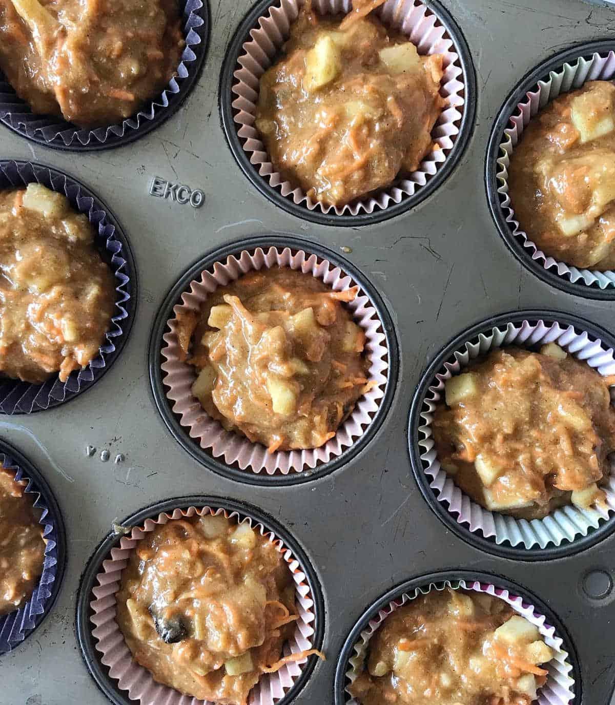 Unbaked muffins in grey metal pan