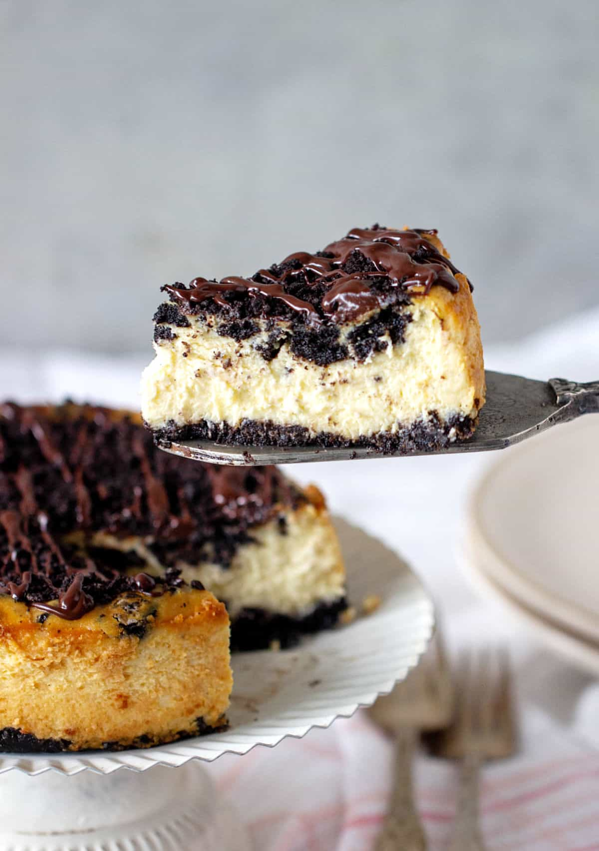 Whole oreo cheesecake on white cake stand with single slice floating above in silver cake server