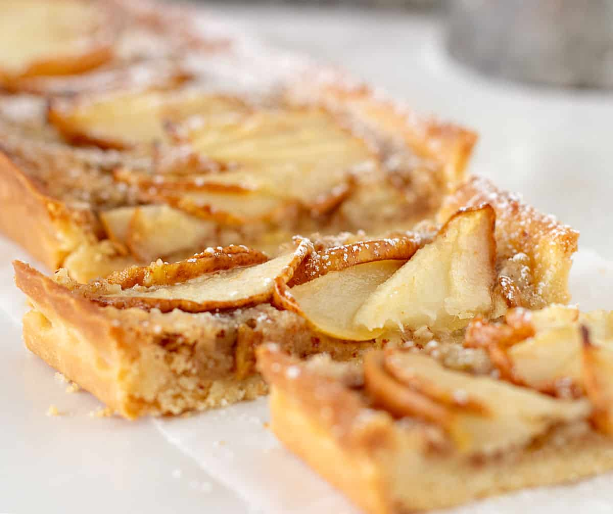 Close up of rectangular pear tart on white parchment paper