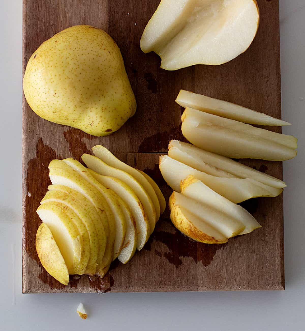 Fresh pear slices and halves on a wooden board