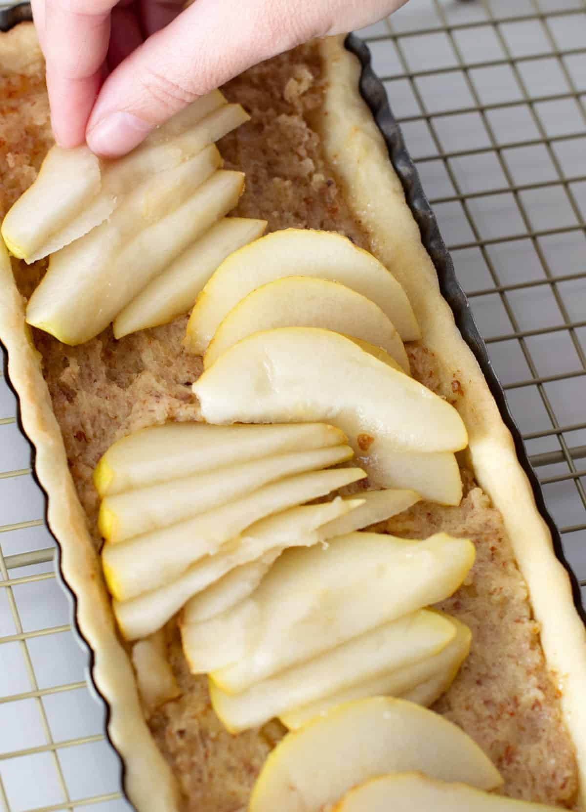 Adding pear slices by hand to long almond tart on a golden wire rack