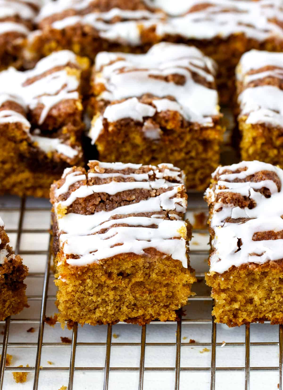 Rows of glazed squares of pumpkin cake on wire rack