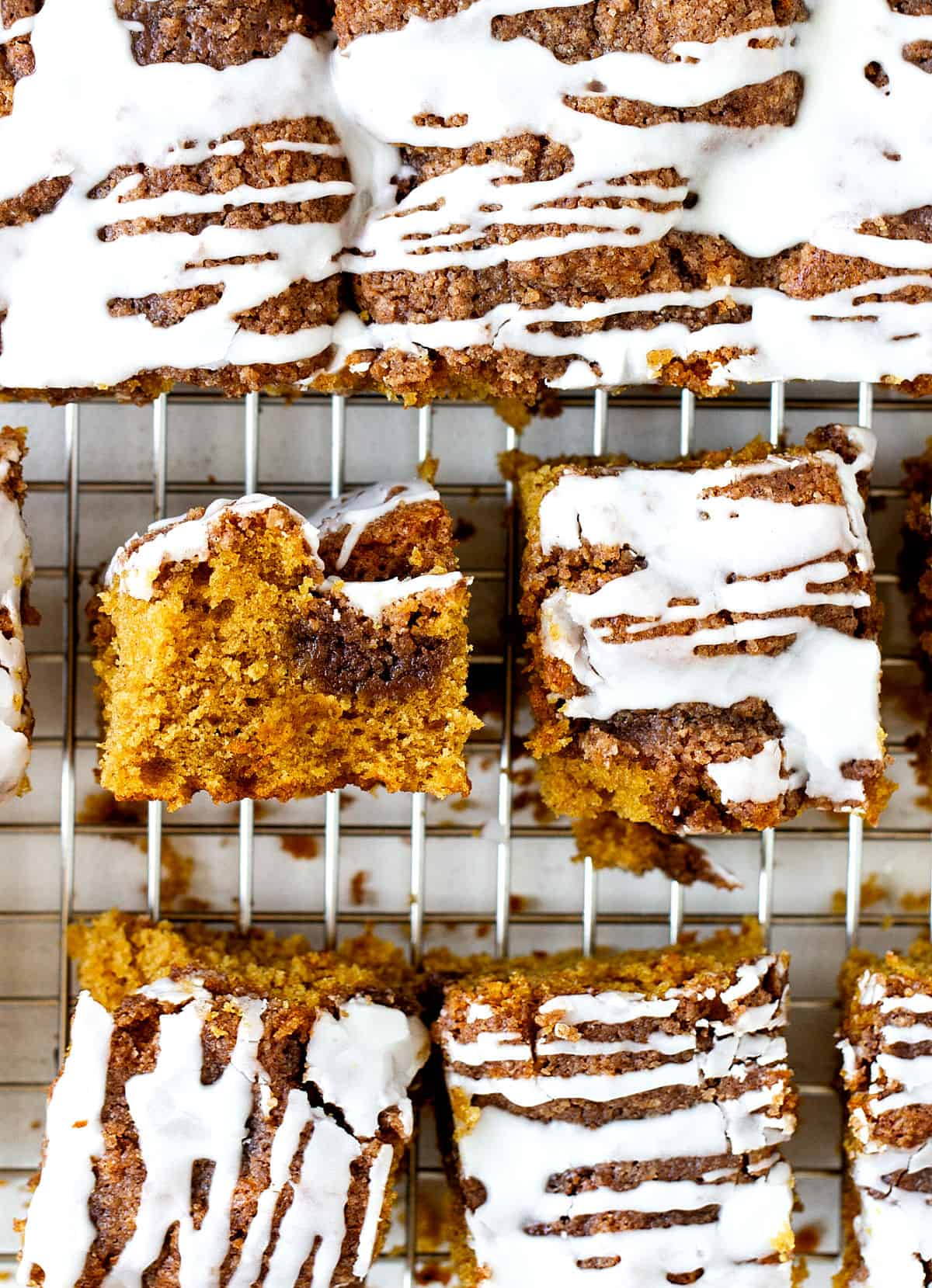 Several squares of iced pumpkin cake on a metal wire rack