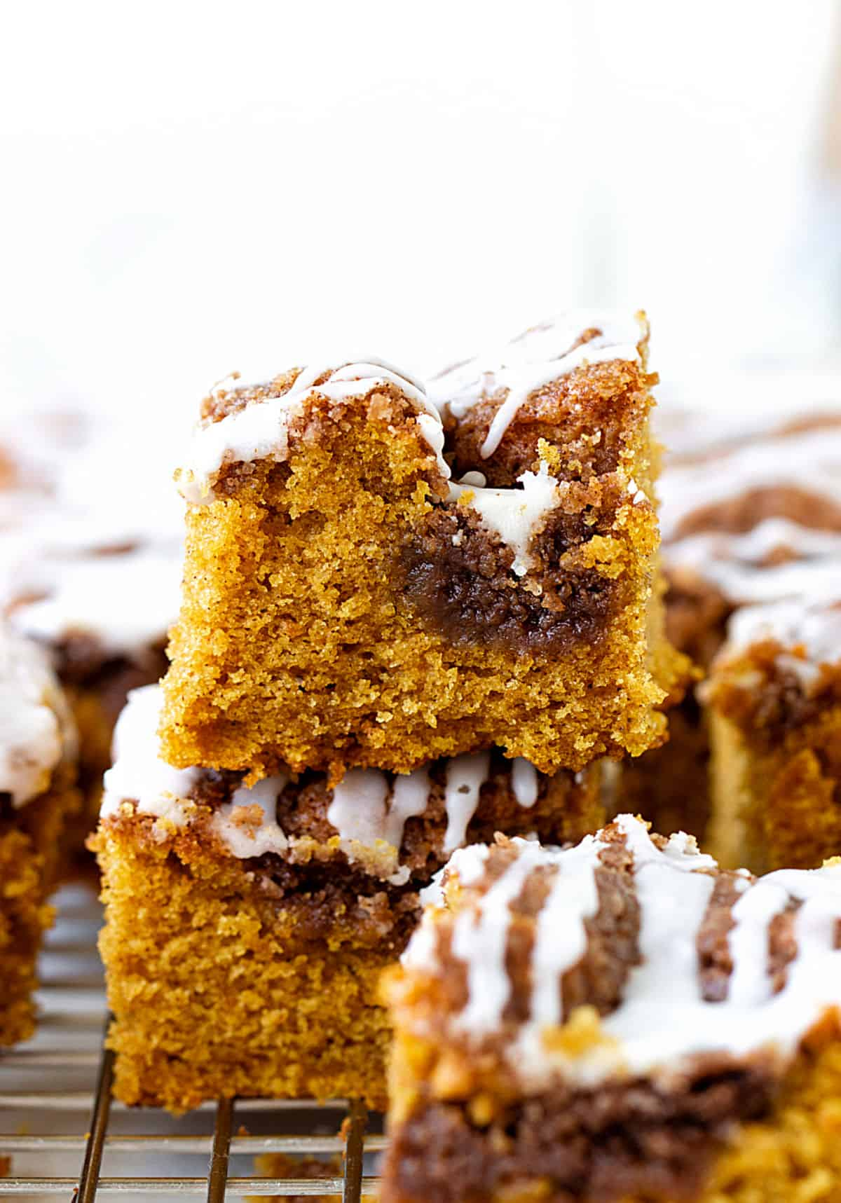 Stacked iced pumpkin coffee cake squares on wire rack, white background
