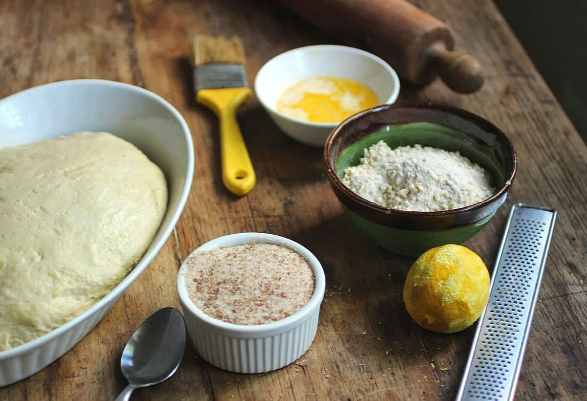Mise en place for sweet potato bread, including dough, lemon, crumble, brush, grater on a wooden table