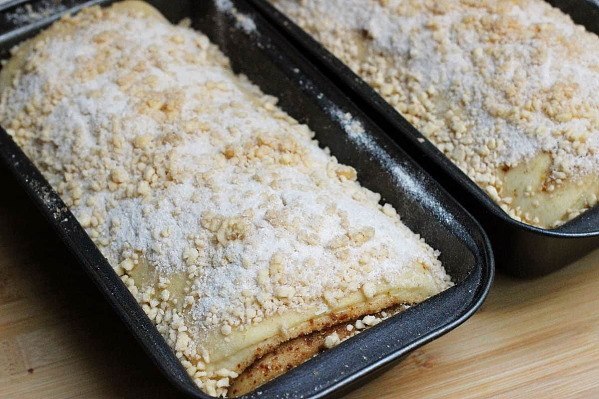 Two metal loaf pans with unbaked bread with crumble topping