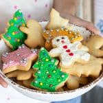 Holding white plate with frosted Christmas sugar cookies