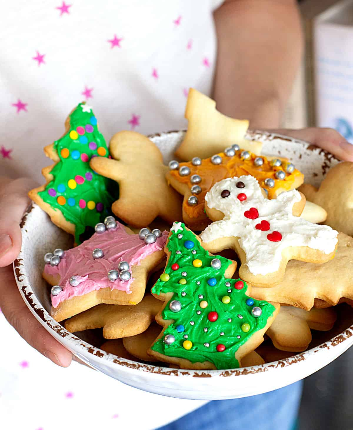 Person holding white shallow bowl with different frosted colorful Christmas cut out cookies