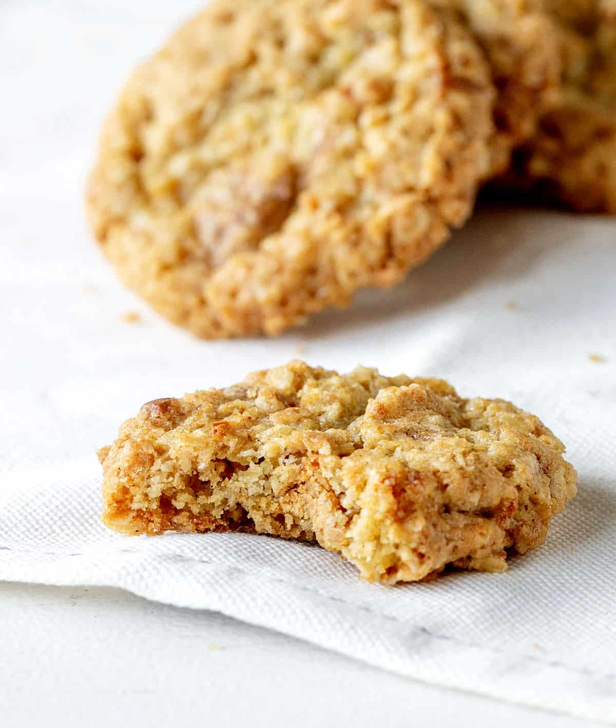 A bitten oatmeal cookie on a white cloth and several others in background