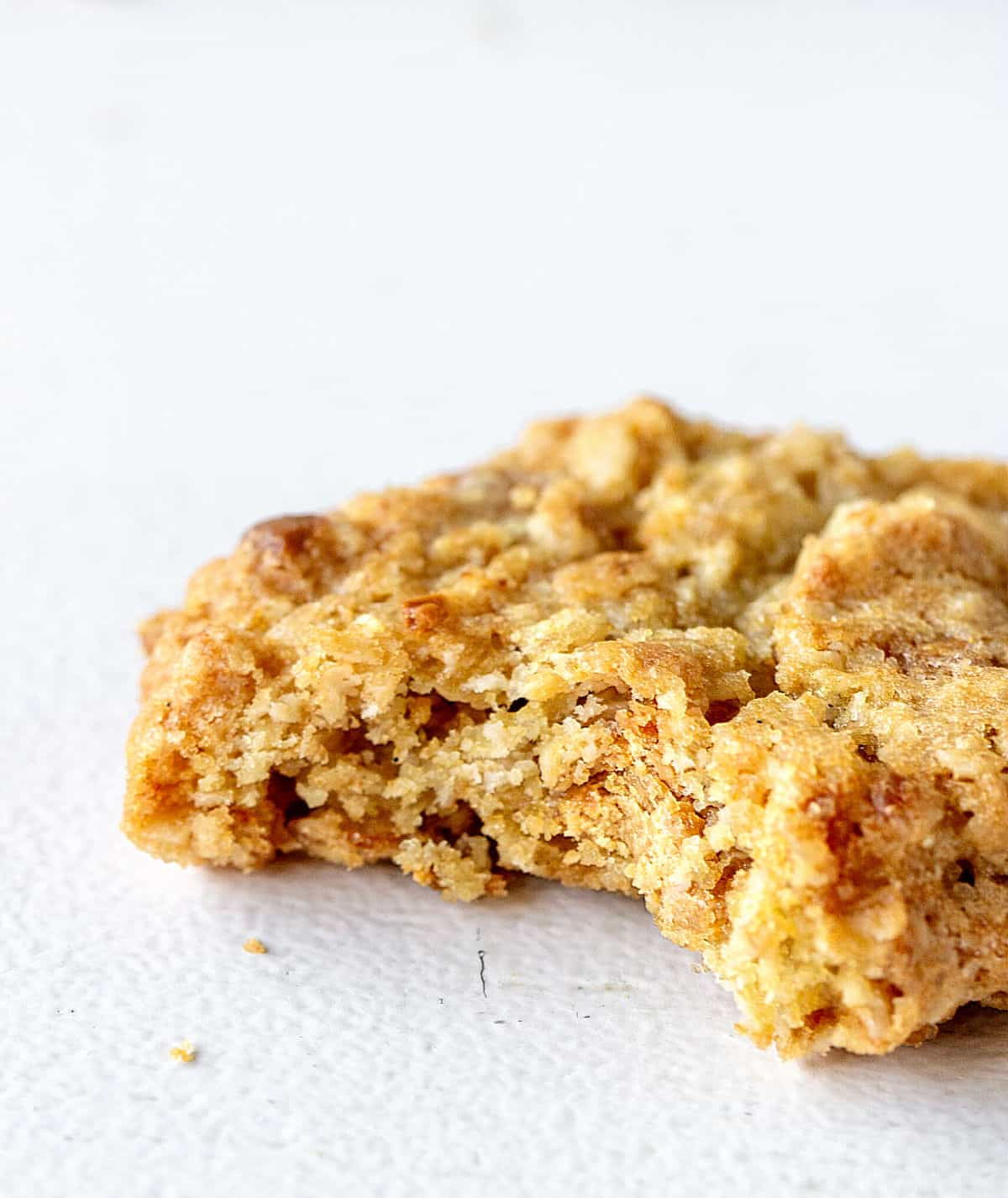 Single bitten oatmeal cookie on a white surface