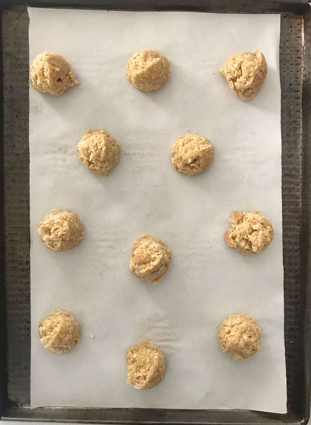 White parchment paper with unbaked oatmeal cookie mounds on a dark metal sheet