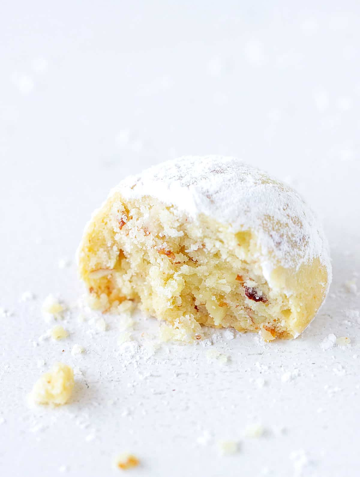 Crumbly round butter cookie, bitten, white surface with crumbs and powdered sugar