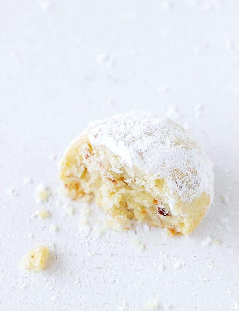 Top view of half a wedding cookie on a white surface, crumbs around