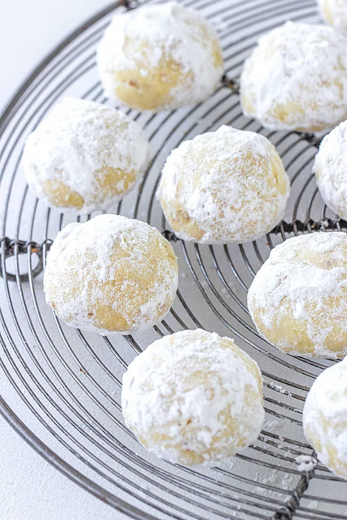 Round metal wire rack with powdered sugar covered snowball cookies