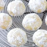 Top view of powdered sugar covered round cookie on wire rack