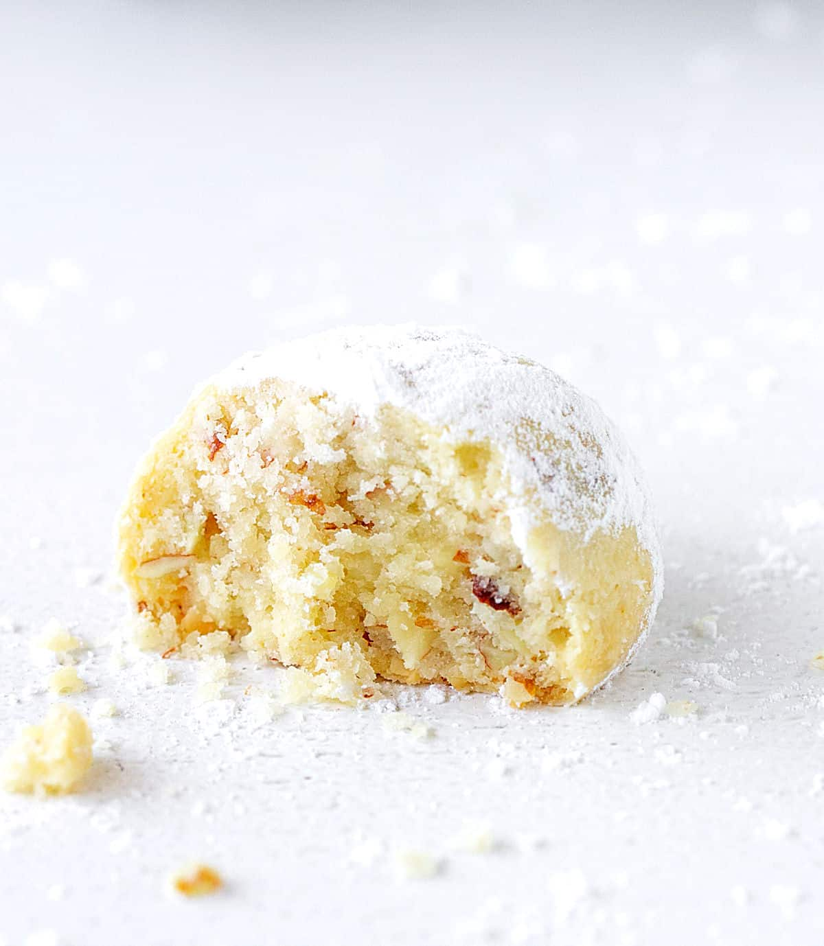 Single half of buttery cookie dusted with powdered sugar on a white surface, crumbs around
