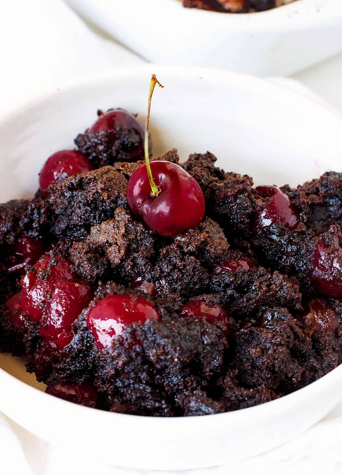 Cherry chocolate dump cake portion in a white bowl on white surface