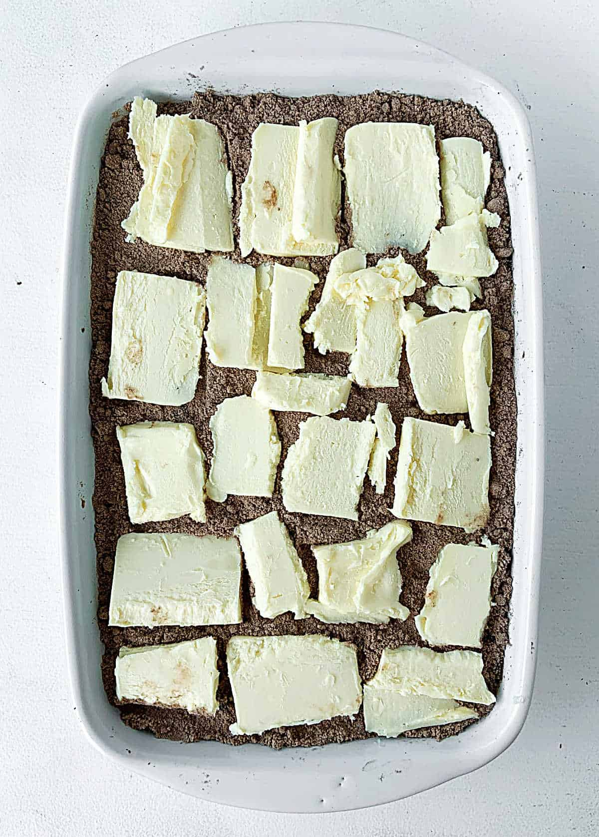 Butter pieces covering chocolate cake mix in rectangular white dish on white surface