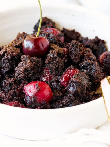 White bowl with chocolate cherry dump cake, a spoon
