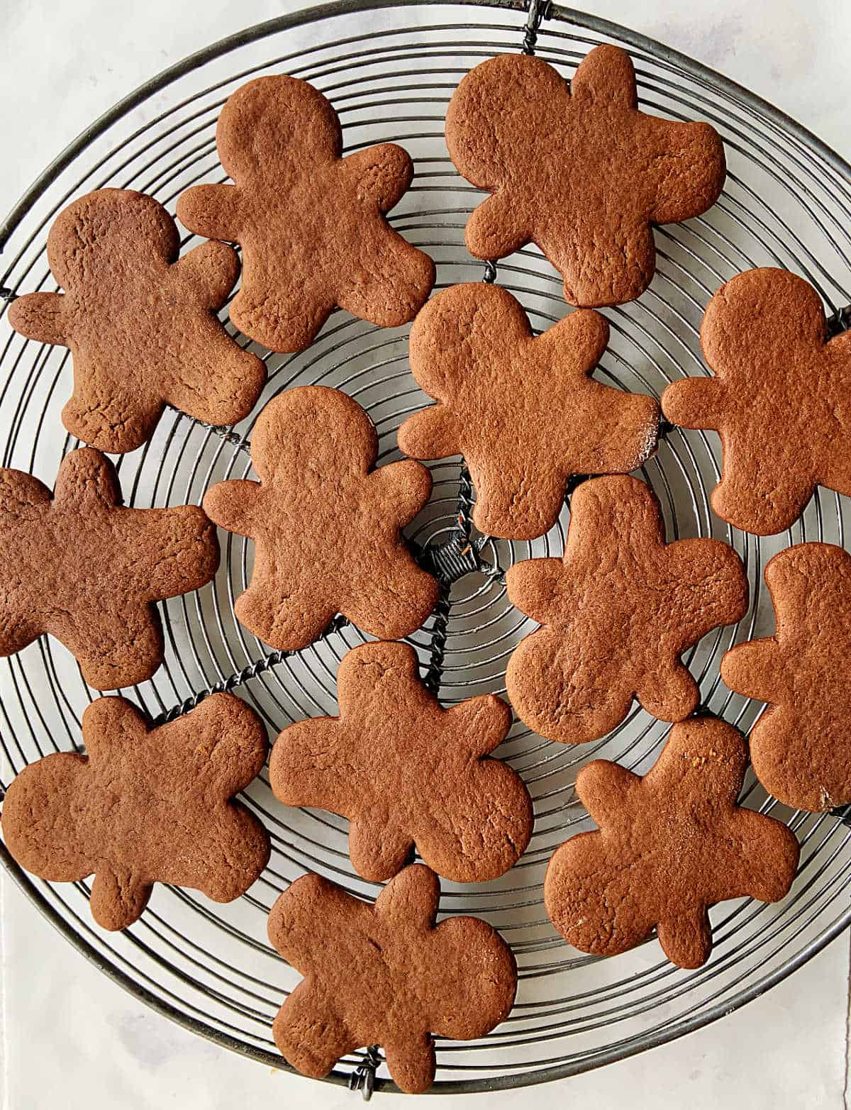 Plain gingerbread people cookies on a round wire rack, white surface