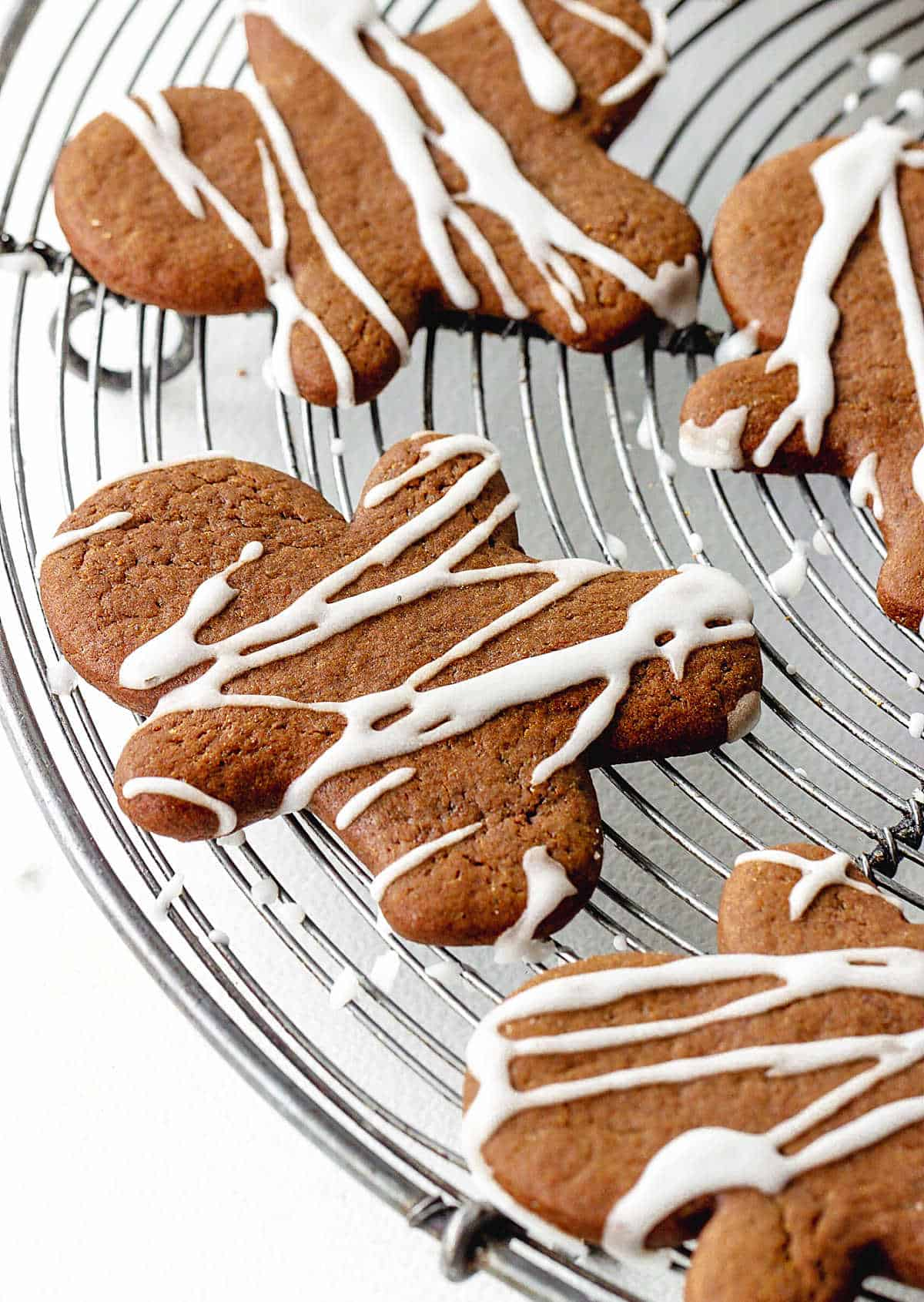Several gingerbread men cookies with icing on a round wire rack