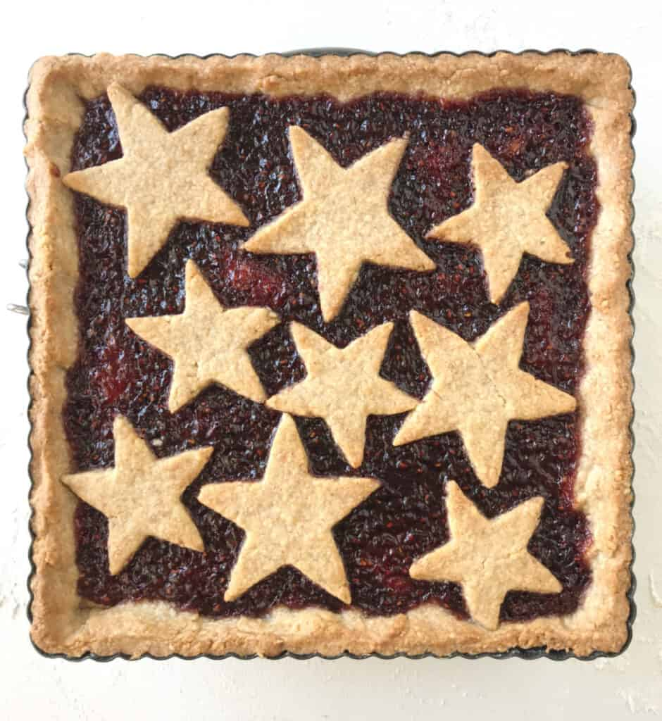 Top view of baked square linzer torte with star cut outs on white surface