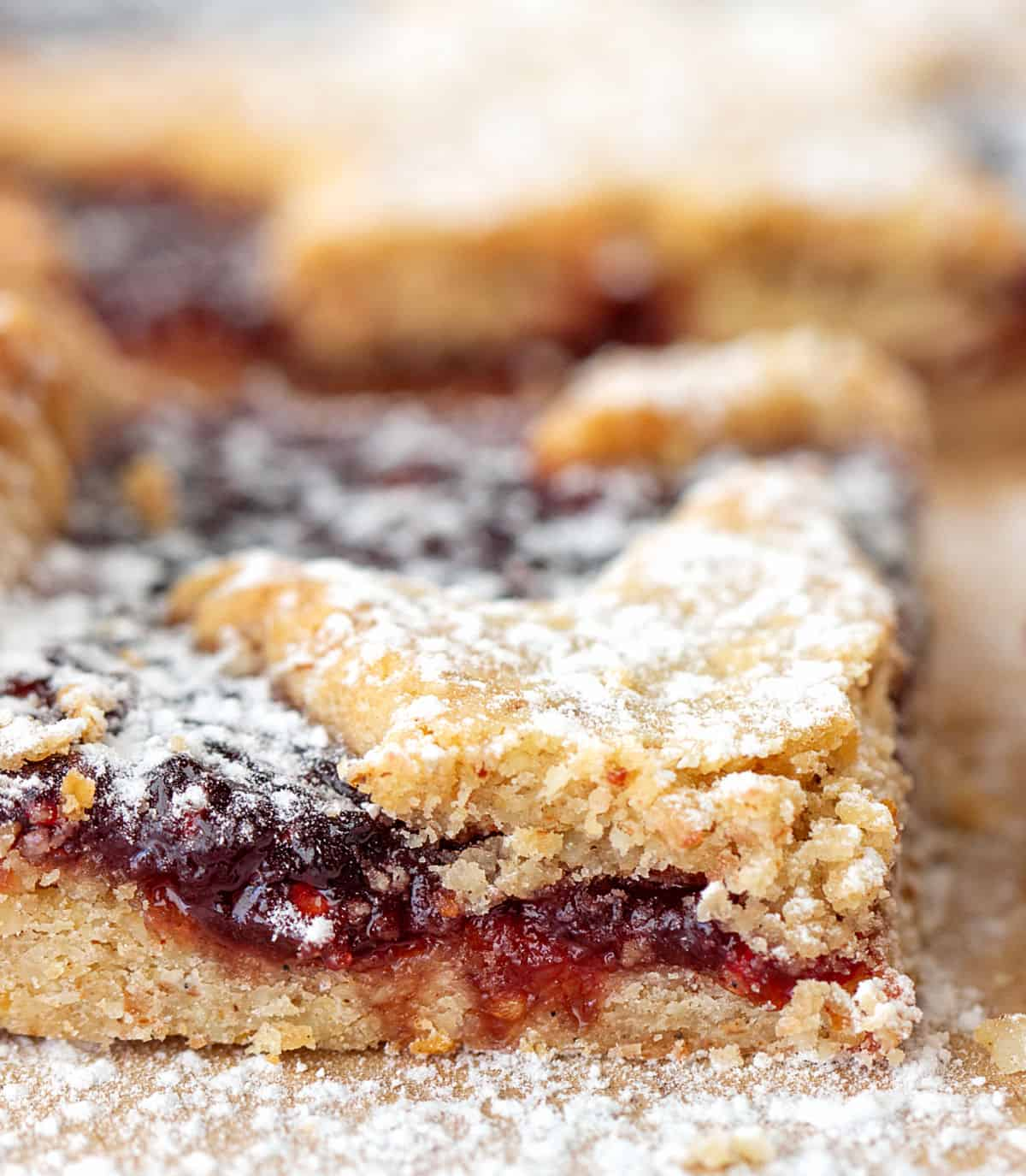 Close up of linzer square with raspberry jam and crumbly dough dusted with powdered sugar