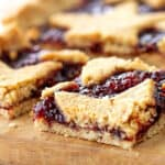 Crumbly square of raspberry linzer tart on wooden board