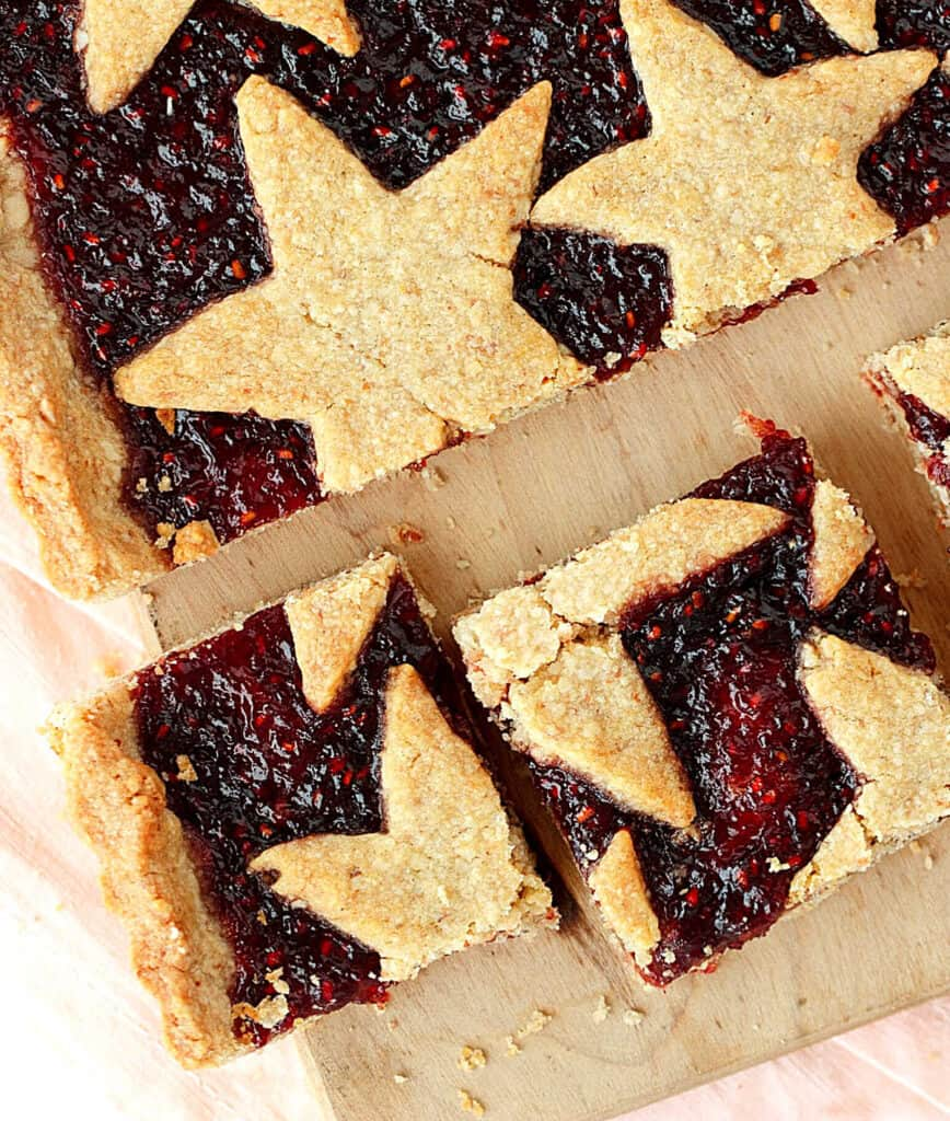 Overview of linzer torte squares with stars on a pink light brown surface