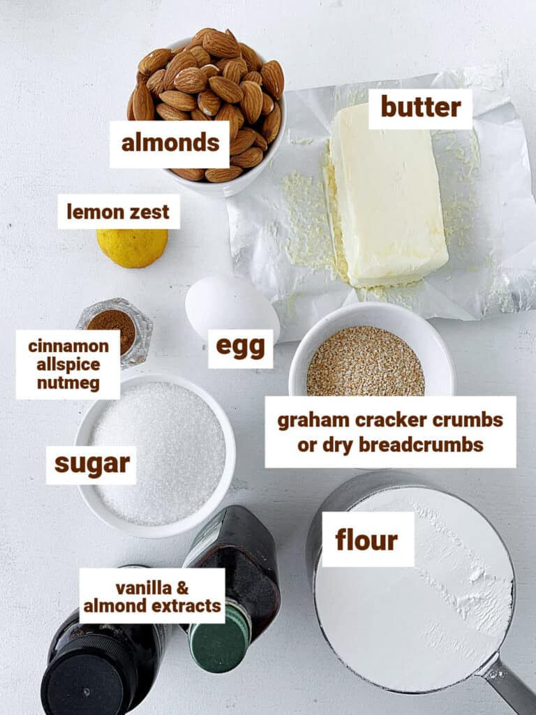 On white surface, bowls and bottles with ingredients for spice dough including almonds and butter