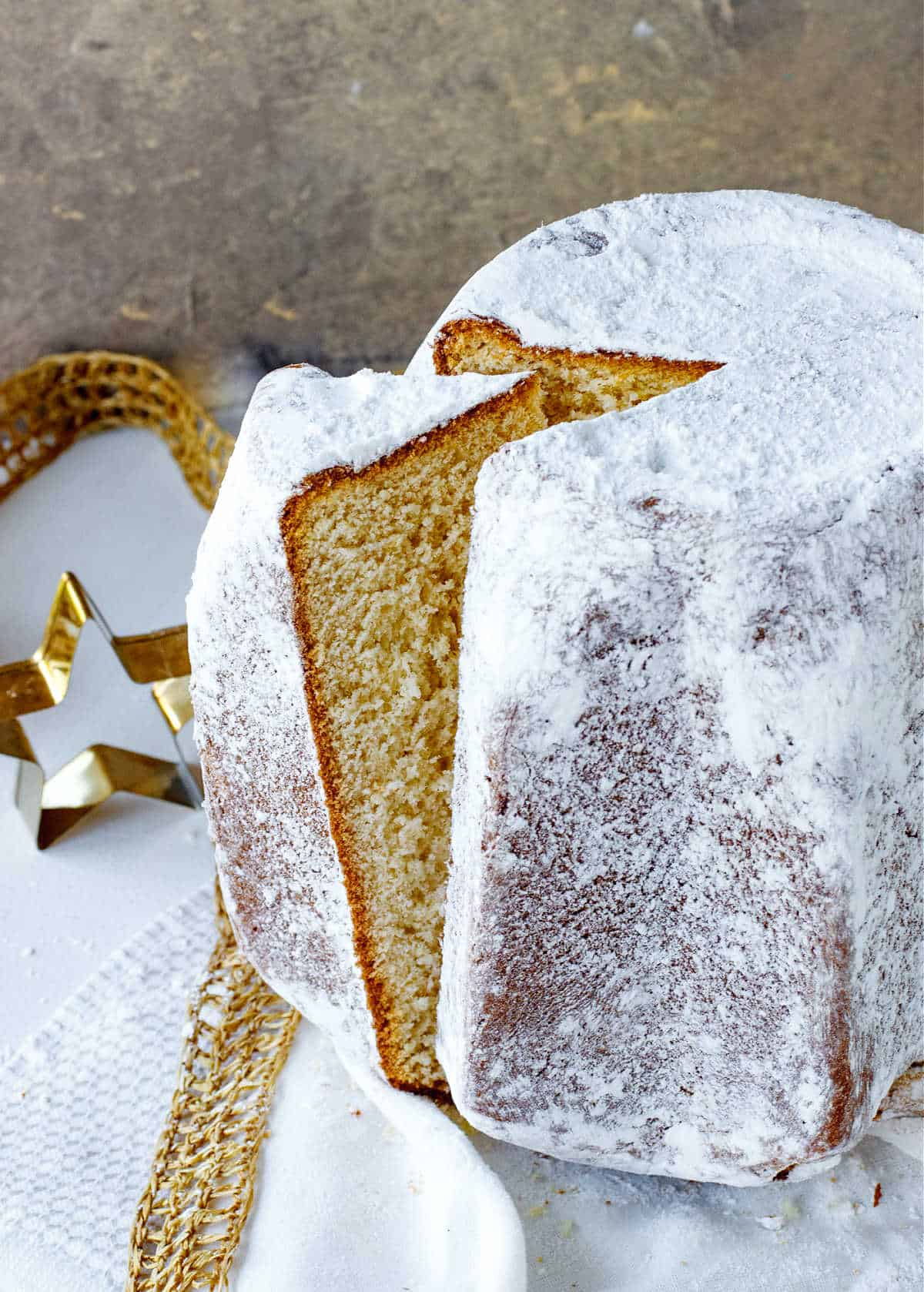 Top view of slice coming out of a whole pandoro bread with powdered sugar; white gold surface and background