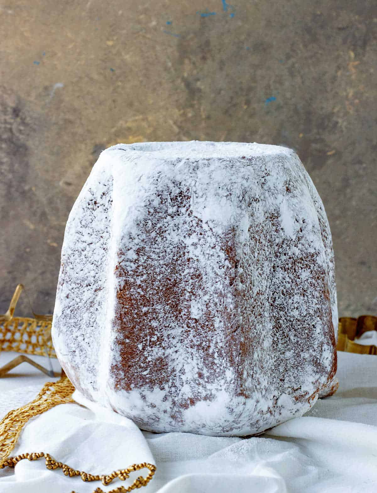 Whole pandoro bread covered in powdered sugar on white golden background