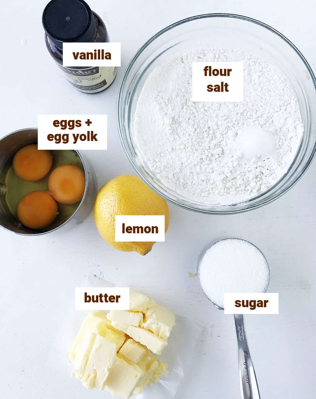 White surface with bowls for pandoro ingredients including lemon, vanilla and eggs