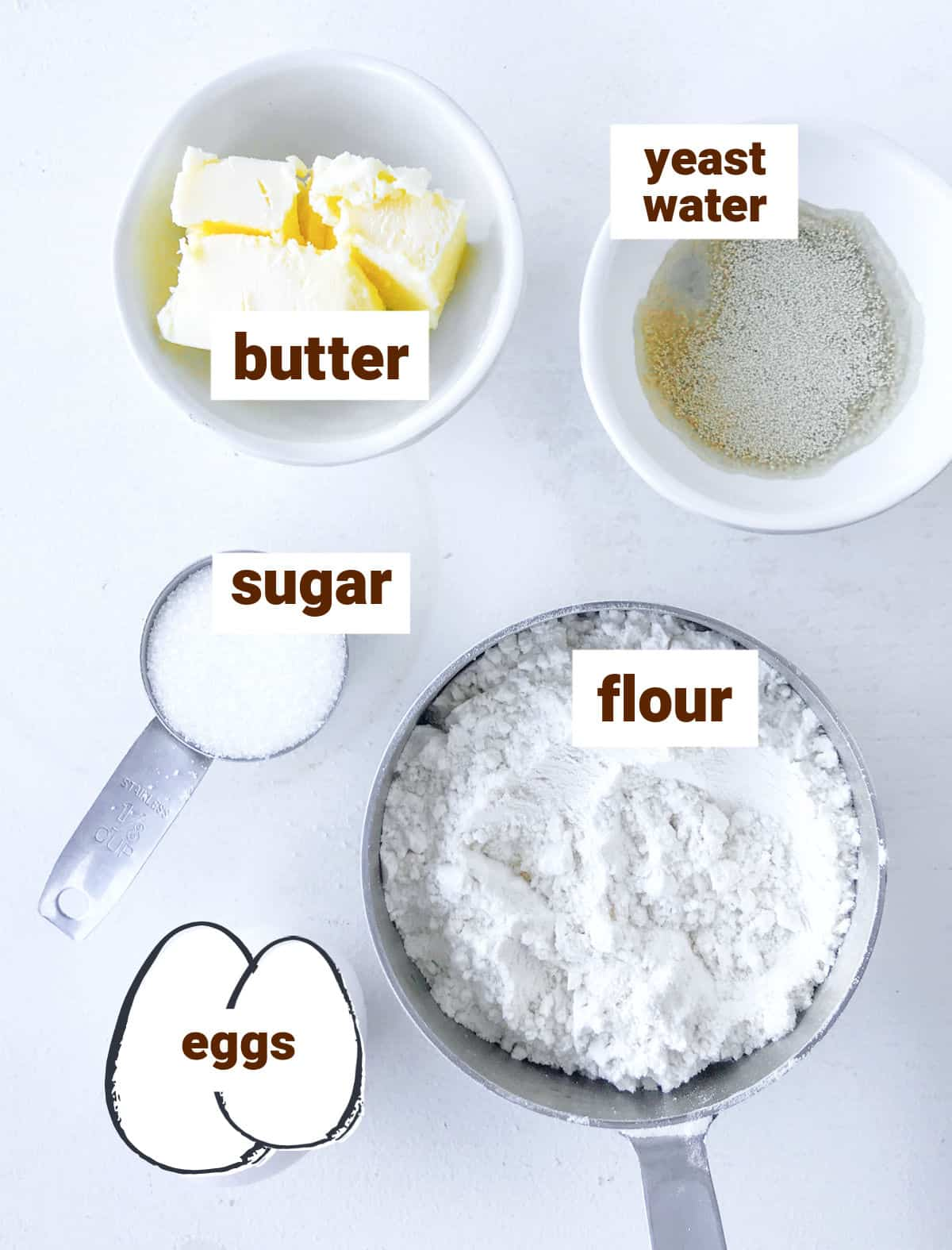 Ingredients in bowls on white surface for pandoro bread, including egg drawing, butter and yeast