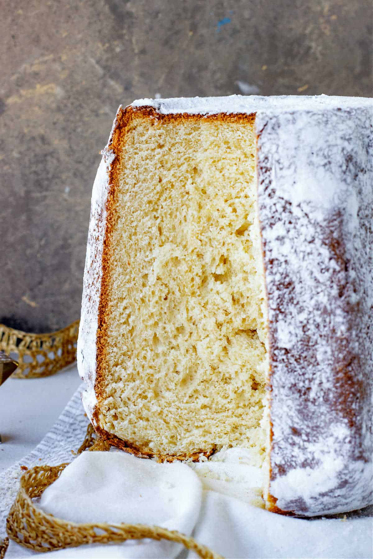 Front view of pandoro bread with missing slice on white, gold and grey surface and background