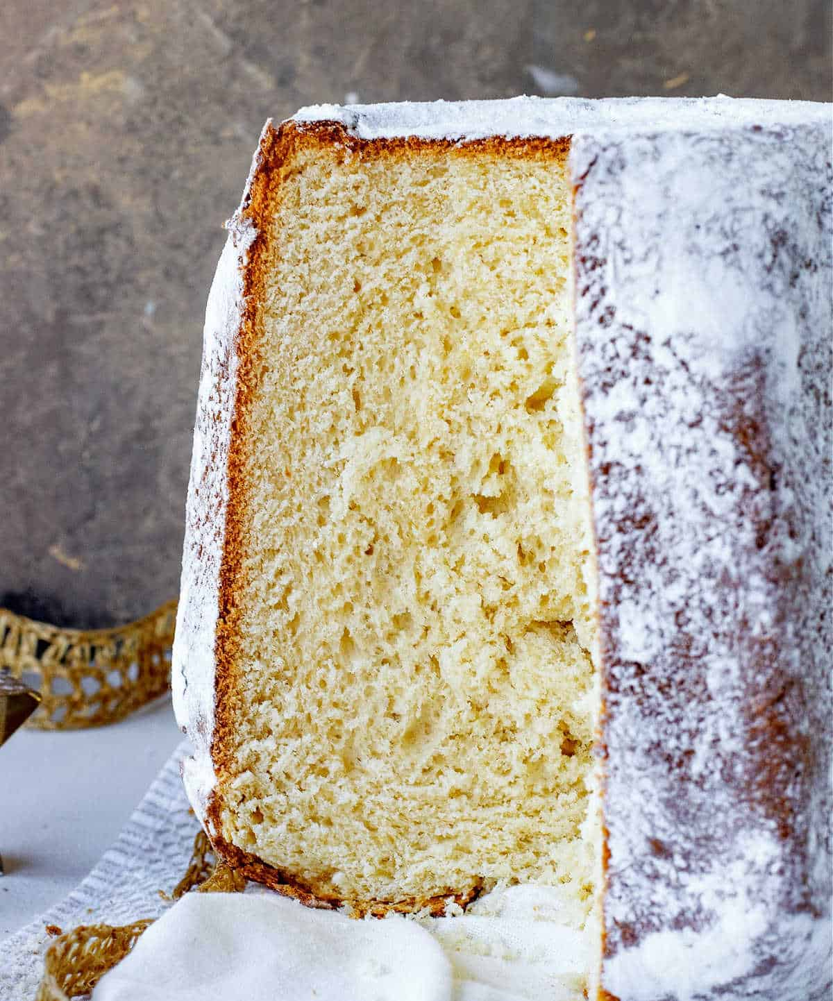 Pandoro bread with exposed crumb on white cloth and golden brown background