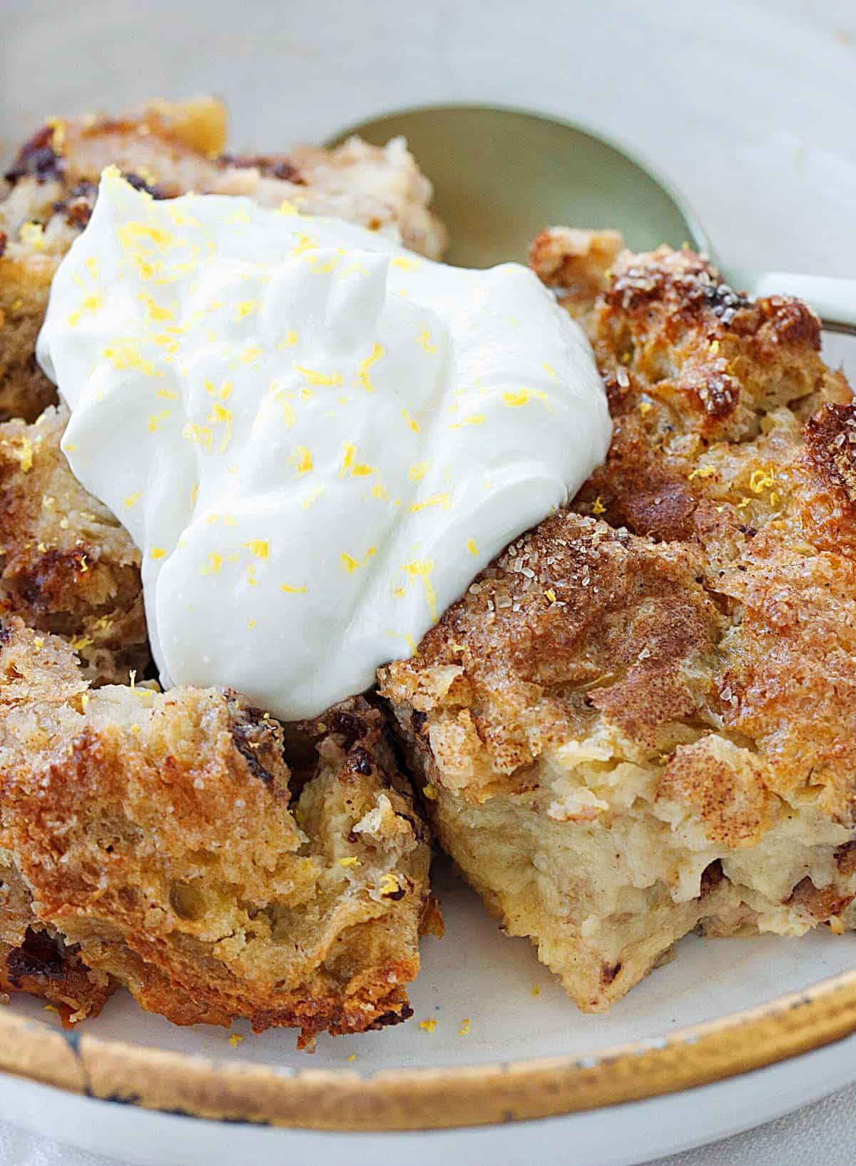 Close up of panettone bread pudding topped with cream on gold rimmed bowl