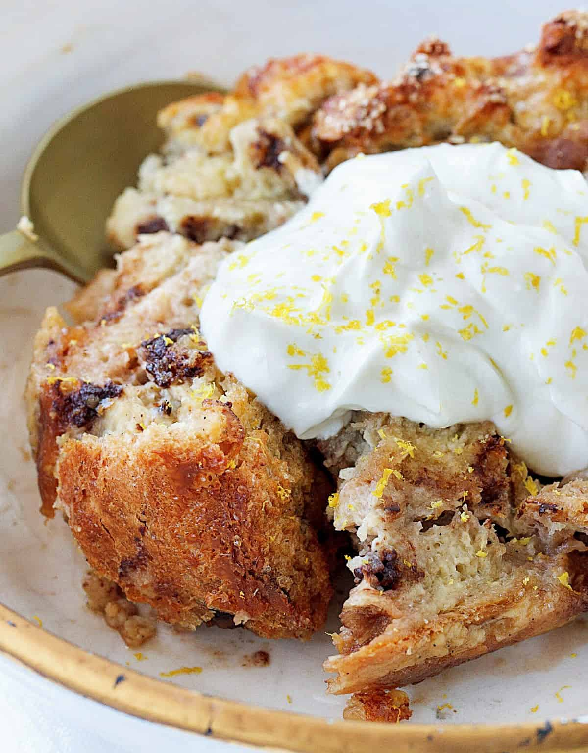 A serving of panettone bread pudding with whipped cream, white gold bowl and spoon