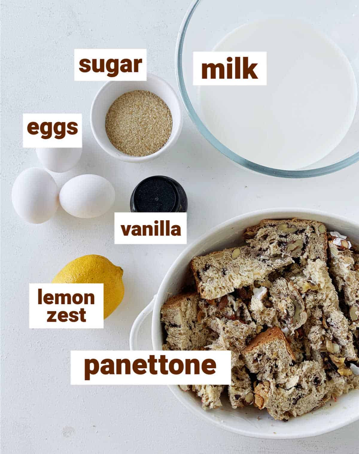 White surface with panettone bread pudding ingredients, including lemon, vanilla and eggs