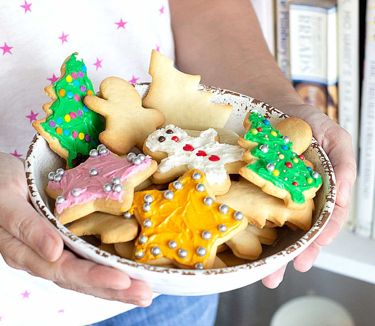 White bowl with frosted sugar cookies held by person with white stars t-shirt