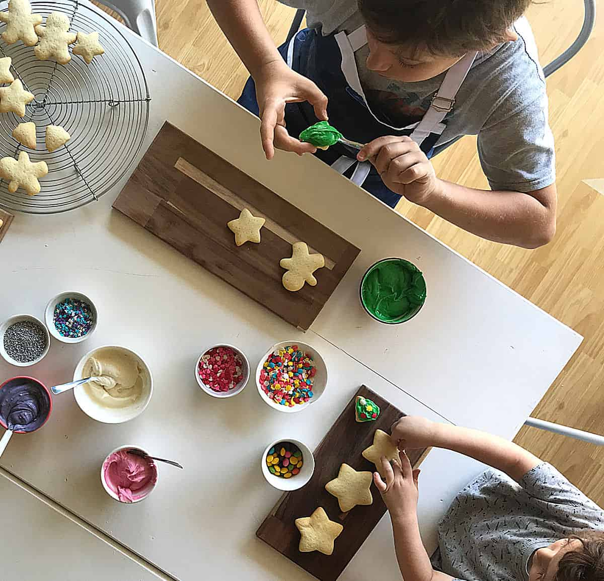 Top view of kids decorating sugar cookies on white table, bowls with colored frosting and sprinkles