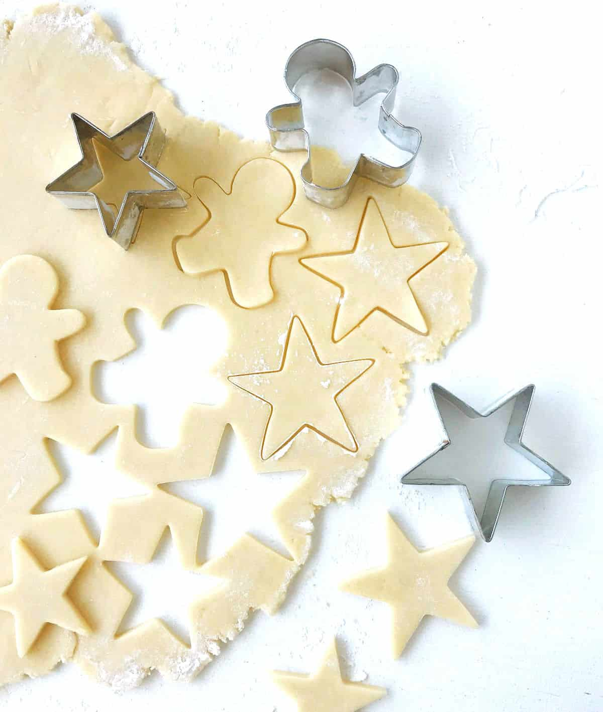 Rolled sugar cookie dough with cut outs and metal cookie shapes, on white surface