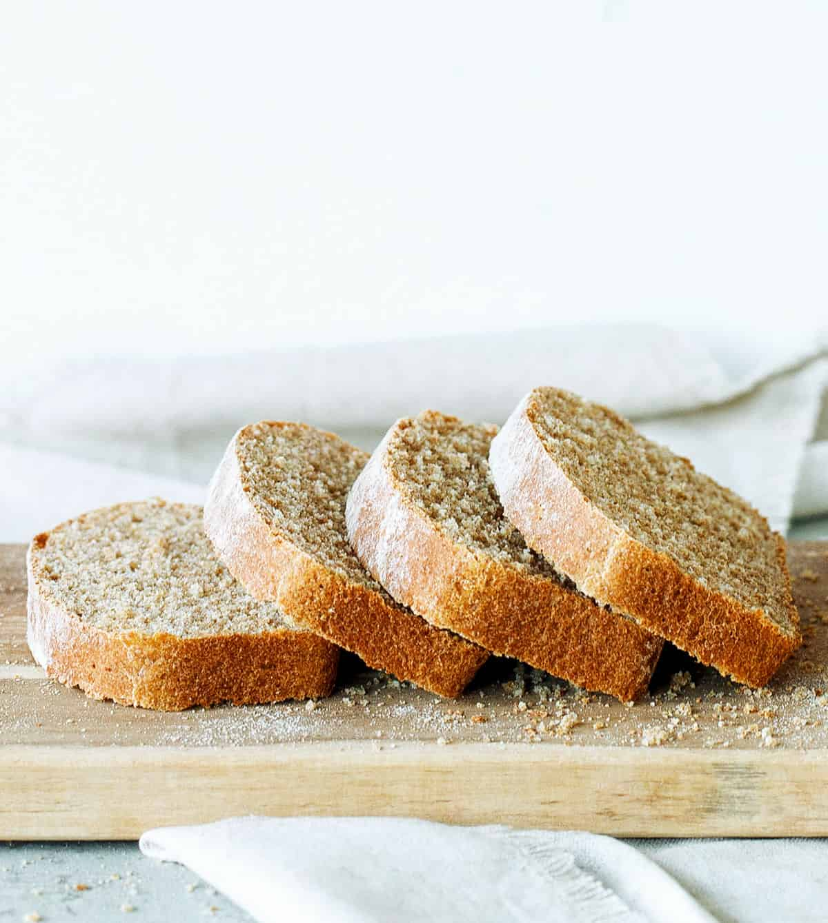 Four slices of whole wheat sandwich bread leaning onto each other on a light wooden board