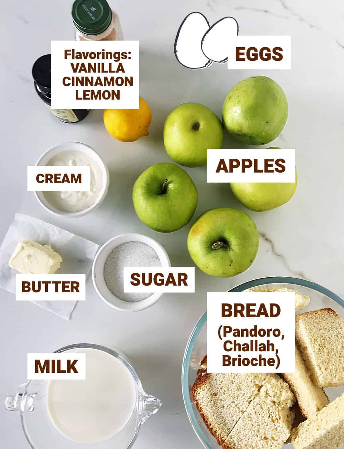 Ingredients for apple bread pudding in bowls and on white surface, including eggs and small bottles