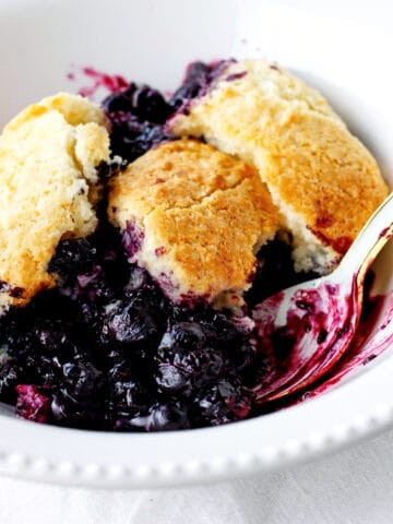 White bowl with serving of blueberry cobbler, a spoon