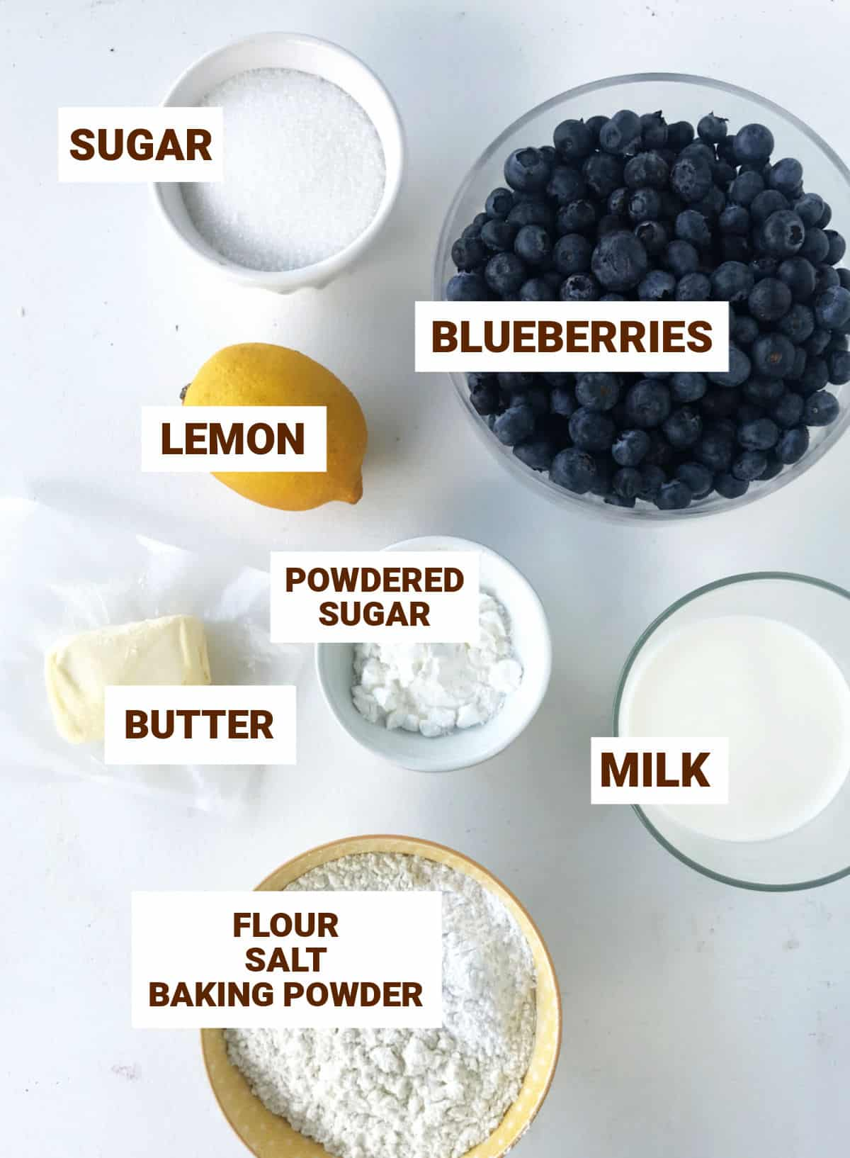 Bowls with ingredients for blueberry lemon cobbler on a white surface