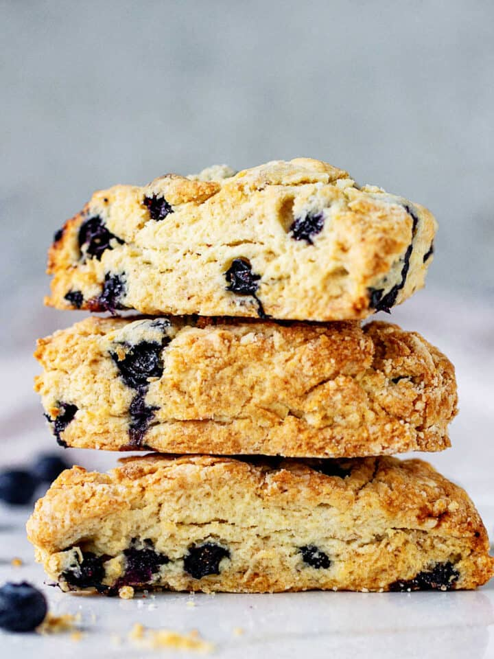 Stack of three blueberry scones on white surface and grey background
